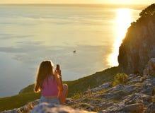 有一个电话的一个少年在她的手上 在日落的美好的夏天场面 免版税库存图片