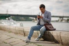有一个电话的商人在河背景 发短信的雇员户外 企业交谈概念 复制空间 免版税库存图片