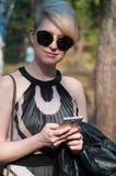 有一个电话的女孩在她的手上 免版税库存照片