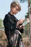 有一个电话的女孩在她的手上 免版税库存图片