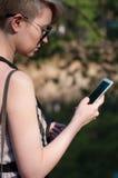 有一个电话的女孩在她的手上 库存照片