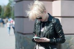 有一个电话的女孩在她的手上 库存图片