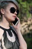 有一个电话的女孩在她的手上 图库摄影