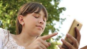 有一个电话的女孩少年在她的手纸卷通过传感器屏幕 E 青年活动在公园 影视素材