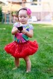 有一个电话的小女孩在一条红色裙子 库存照片