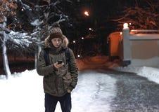 有一个电话的年轻人在一条城市街道在一个冷淡的晚上 免版税库存照片