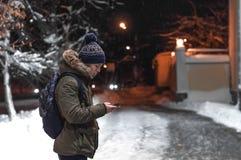 有一个电话的年轻人在一条城市街道在一个冷淡的晚上 库存照片