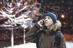 有一个电话的年轻人在一条城市街道在一个冷淡的晚上 免版税库存图片