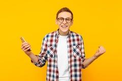 有一个电话的成功的人,在黄色背景 免版税库存照片