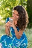 有一个电话的青少年的女孩在公园 免版税库存图片