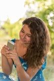 有一个电话的青少年的女孩在公园 库存照片