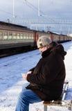 有一个电话的年长人在他的手等待的火车 免版税库存图片