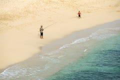 有一个男孩的未知的渔夫有在海滩的钓鱼竿的 图库摄影