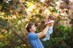 有一个男婴的他的胳膊的,特写镜头,夏天爸爸 图库摄影
