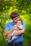 有一个男婴的他的胳膊的,特写镜头,夏天爸爸 免版税图库摄影