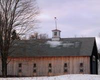 有一个白色圆屋顶的美丽的新英格兰木谷仓在多云进入天 免版税库存图片