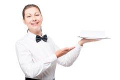 有一个盘子的愉快的30岁的女服务员在白色 库存图片