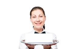 有一个盘子的愉快的30岁的女服务员在白色 免版税库存图片