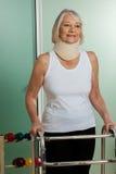 有一个矫形脖子的妇女使用步行者 免版税库存照片