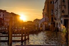 有一个码头的大运河在日落的长平底船的在威尼斯 免版税库存图片