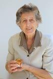 有一个礼物的一名资深妇女在她的棕榈 免版税库存图片