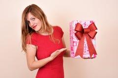 有一个礼物的圣诞节肉欲的女孩,在红色服装 库存图片