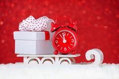 有一个礼物盒的红色时钟在雪的雪橇在红色背景 免版税库存照片
