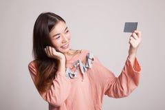 有一个空插件的愉快的年轻亚裔妇女 库存照片