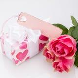 有一个空标识符的礼物盒,在三朵玫瑰旁边 免版税图库摄影