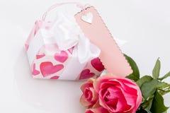 有一个空标识符的礼物盒,在三朵玫瑰旁边 库存照片