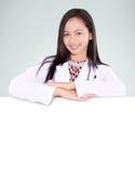有一个空白的委员会的一位微笑的女性医生 免版税图库摄影