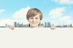 有一个空白的广告牌的男孩 免版税库存照片