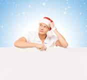 有一个空白的广告牌的英俊的年轻人在圣诞节背景 免版税库存照片