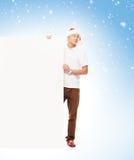 有一个空白的广告牌的英俊的年轻人在圣诞节背景 图库摄影