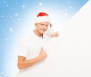 有一个空白的广告牌的英俊的年轻人在圣诞节背景 免版税图库摄影