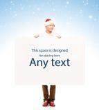 有一个空白的广告牌的英俊的年轻人在圣诞节背景 免版税库存图片