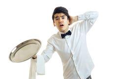 有一个空的盘子的年轻侍者碗柜的张了他的嘴并且保留了头的球 免版税图库摄影