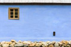 有一个窗口和石头基地的蓝色墙壁 免版税库存照片