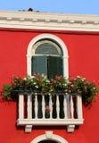 有一个窗口的开花的阳台在房子和许多花盆里 免版税库存照片