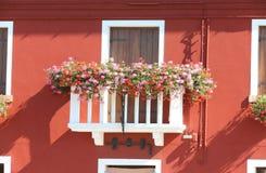 有一个窗口的开花的阳台在房子和许多花盆里 图库摄影