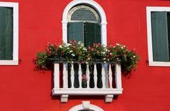 有一个窗口的开花的阳台在房子和许多花盆里 库存照片