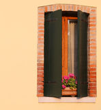 有一个窗口的开花的阳台在房子和许多花盆里 库存图片