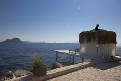 有一个竹屋顶和一个小码头的白色平房在seasho 免版税库存图片