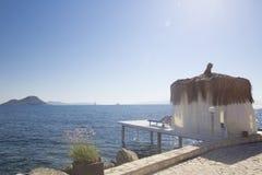 有一个竹屋顶和一个小码头的白色平房有白色的 免版税库存照片