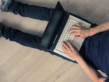 有一个笔记本的人在地板上 免版税图库摄影
