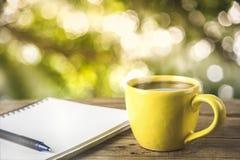 有一个笔记本的咖啡杯在一张桌上在树下 库存图片