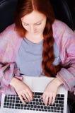 有一个笔记本的妇女在椅子 免版税库存照片
