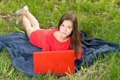有一个笔记本的美丽的女孩在公园 免版税图库摄影