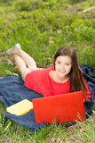 有一个笔记本的美丽的女孩在公园 免版税库存照片