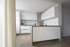 有一个简单设计的现代,明亮的白色厨房 免版税库存照片